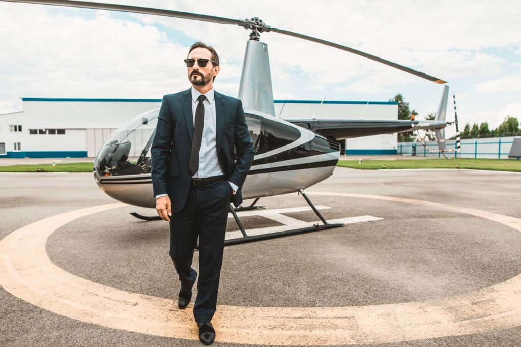 Confident businessman wearing glasses and walking from the helicopter
