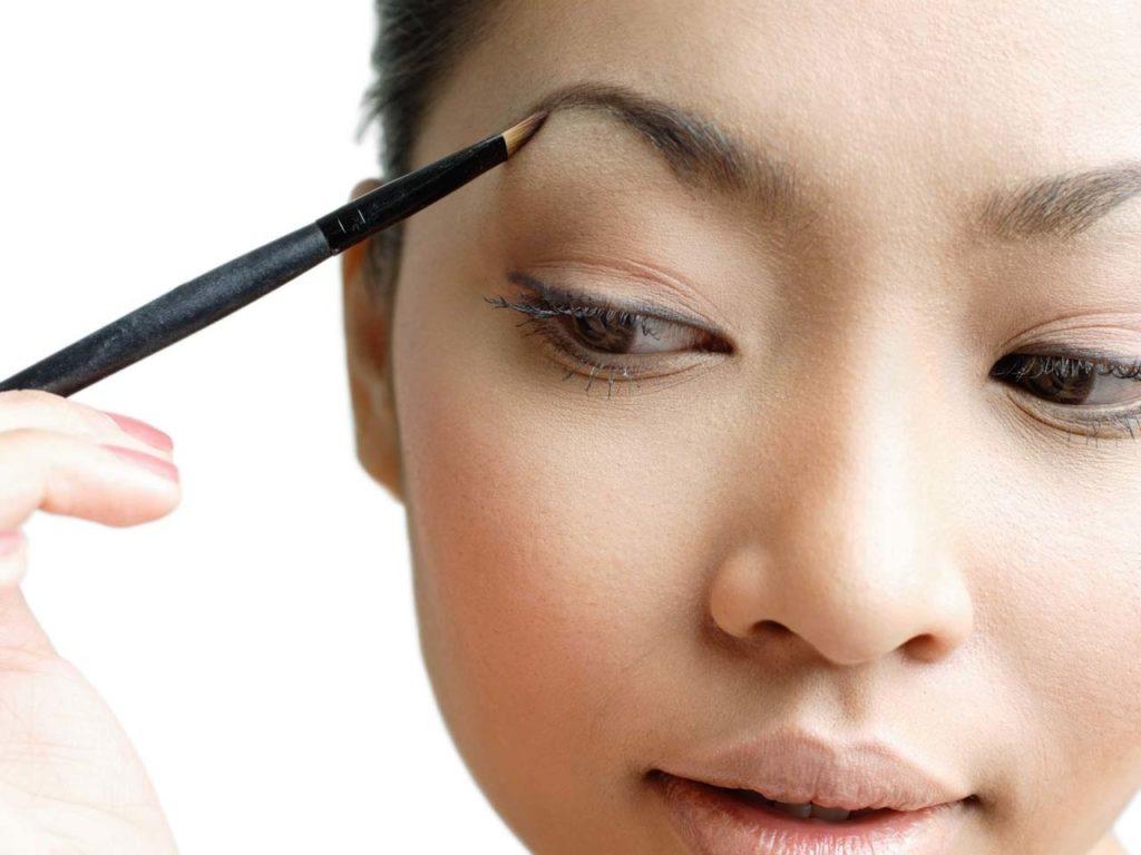 Young woman holding eyebrow pencil to eyebrow