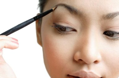 Young woman holding eyebrow pencil to eyebrow