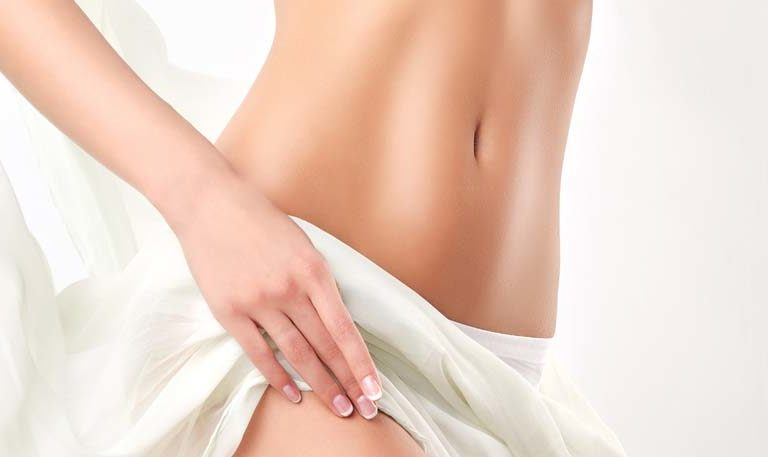 Graceful female body covered by tender, silk textile.  Alluring and healthy woman belly and hips..
